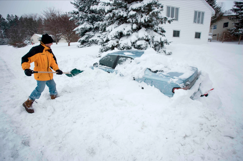 Young Man Digging Out Car After Snow Storm - Ithaca NY