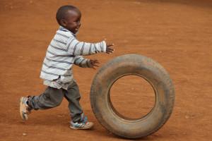 Child playing with tire, near Eldoret, Kenya, Kalingen tribal area
